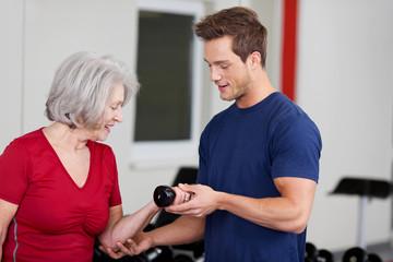 seniorin und trainer im fitnessstudio