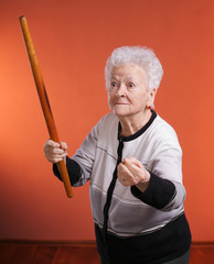 Old angry woman threatening with a rolling pin