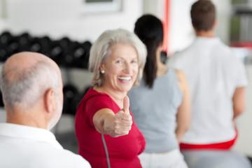 sportliche seniorin zeigt daumen hoch