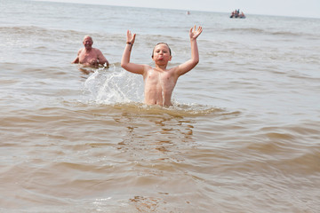 Young boy and grandpa swimming in the ocean. Enjoying the waves.