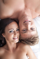 Portrait of smiling beautiful lovers posing in bed