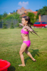 little girl in a swimsuit playing and splashing in the yard