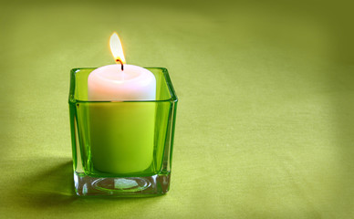 A  candle in glass lamp on a green background