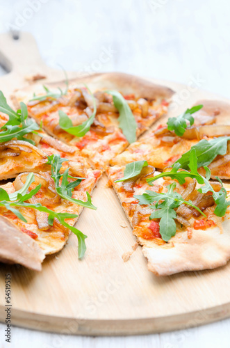 Gourmet thin crust pizza with fresh rocket and caramelised onion