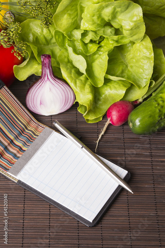 vegetables, notebook and pen on wood