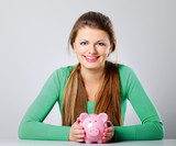 Young beautiful woman with piggy bank (money box)
