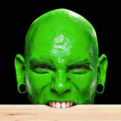 Mann mit grünem Gesicht beißt in Tischkante