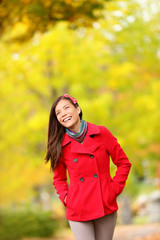 Fall woman walking amongst autumn trees