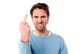 Angry young man showing middle finger