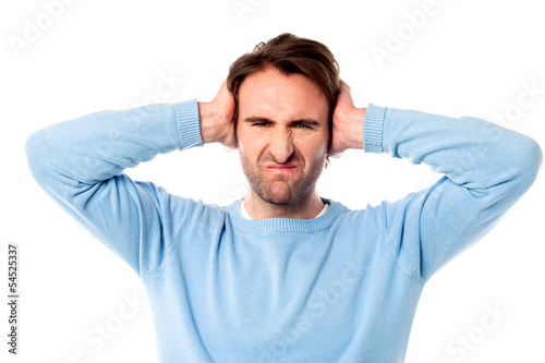 Irritated man blocking his ears
