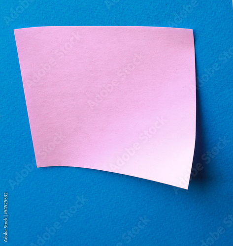Pink paper note on blue background isolated.