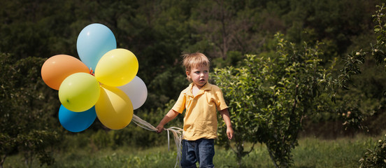 beautiful young man in a spring field with lots of balloons
