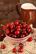 Ripe red cherry berries in bowl on wooden table close-up