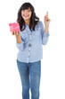 Smiling young woman with piggy bank pointing her finger