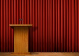 Podium on stage over red curtain