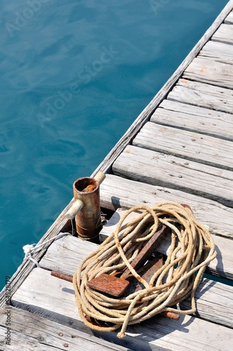 Coiled marine rope and small, old rusted bollard on wooden pier