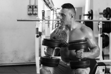 A muscular athlete is preparing to lift two heavy dumbbells