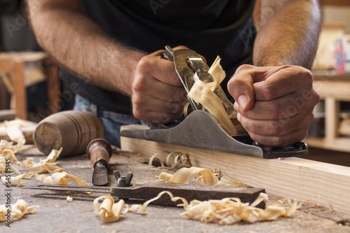 Poster carpenter working  with  plane  on wooden background