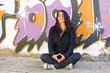 Young woman meditating at a graffiti brick wall