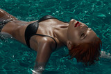 Redahead model laying on water in pool