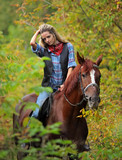 Blond cowgirl riding her horse in autumn woods