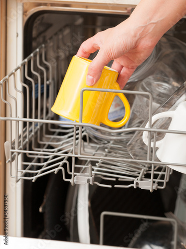 Hand putting a mug into a dishwasher