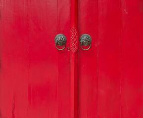 an old wood door red color with metal handle