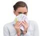 Businesswoman hiding behind money in her hands