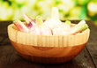 Fresh garlic in bowl, on wooden table, on bright background