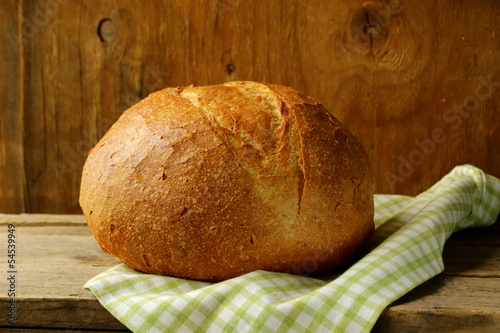 large loaf of homemade bread with a kitchen towel