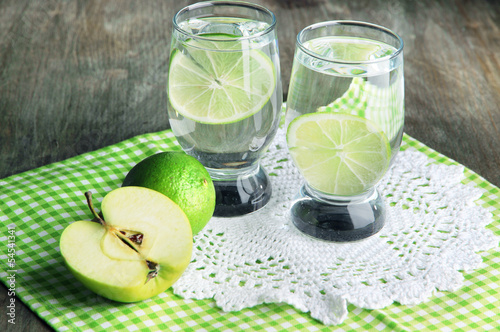 Glasses of cocktail with lime on napkin on dark wooden table