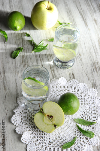 Glasses of cocktail with lime on napkin on light wooden table