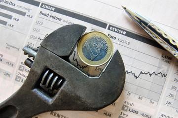 Eurokrise - Schraubenschlüssel mit Euro auf Börsenstatistiken