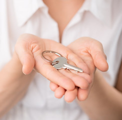 Real estate consultant woman holding a key of a new apartment