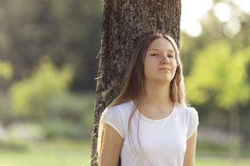 young girl leaning on a tree