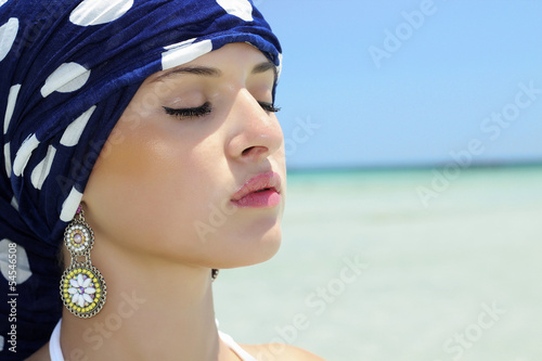 beautiful woman in a blue shawl on the beach. arabian style