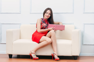 A woman with gift is sitting on the sofa