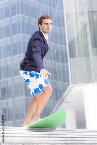 Young businessman with surfboard thinking about vacations