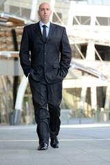 Uomo d'affari che cammina con mani in tasca