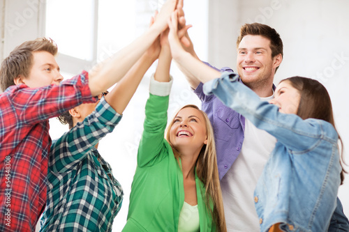 happy students giving high five at school