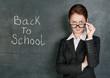Teacher and phrase Back to school on the school blackboard