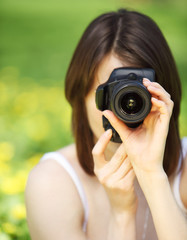 Image of young woman photographing in summer park