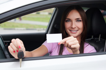 girl in a car showing a key and an empty white card