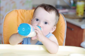 Baby age of 10 months eats from small bottle