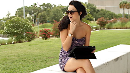 Sexy woman with tablet computer outdoors on windy day