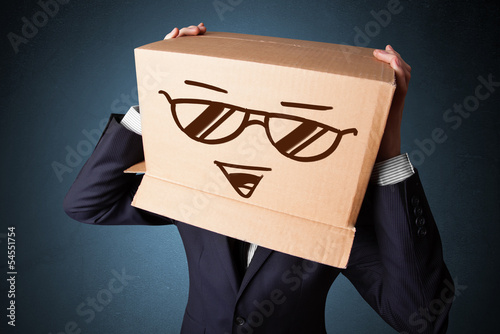 Businessman gesturing with a cardboard box on his head with smil