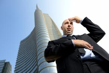 uomo d'affari in difficoltà davanti ai grattacieli