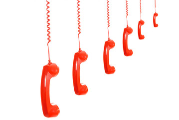 Isolated dangling red retro telephone receivers on white