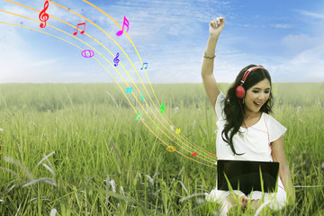 Attractive female listening to music on green field