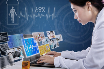 Busy doctor typing on laptop with digital pictures
